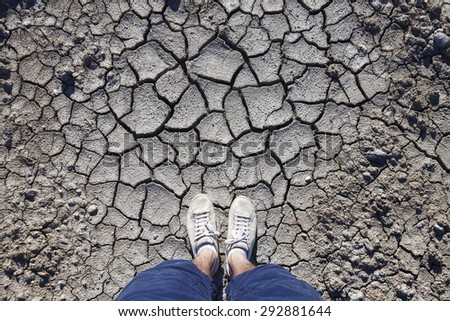 Man with white shoes standing on cracked dried soil ground. Concept photo. Point of view man standing on cracked soil ground. - stock photo