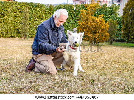 Man with White Swiss Shepherd puppy in the park.