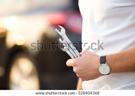 Man with wrench in hands repair car on road - stock photo