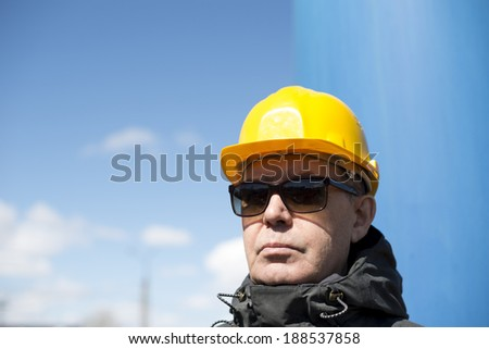 man with yellow hardhat and sunglasses - stock photo