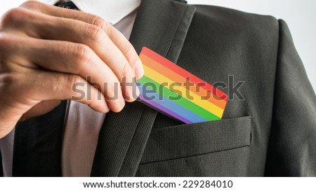 Man withdrawing a wooden card painted as the gay pride flag from his suit pocket, close up of his hand. - stock photo