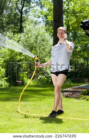 Man without trousers watering the plants in garden