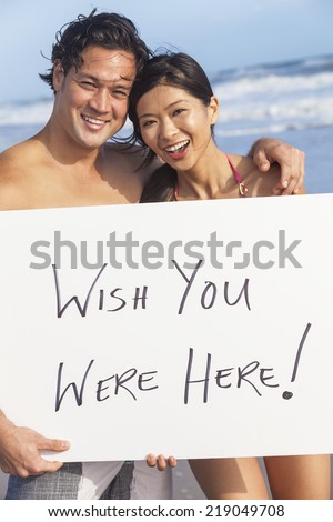 Man & woman Asian couple, boyfriend and girlfriend in bikini, on vacation beach holding Wish You Were Here sign - stock photo