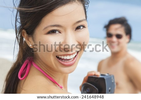 Man & woman Asian couple, boyfriend girlfriend in bikini, taking vacation video or photograph at the beach  - stock photo