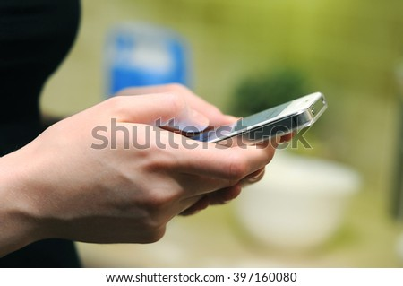 Man woman holds phone in hands and typing by fingers chatting writing in social media , sms, email, notes, diary