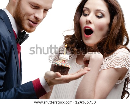 Man wonders his pretty girlfriend with birthday pie, isolated on white - stock photo