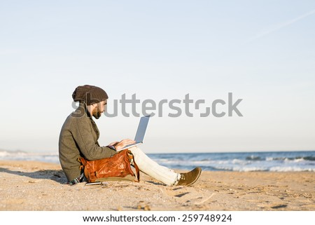 Man work on computer at the beach at sunset - stock photo