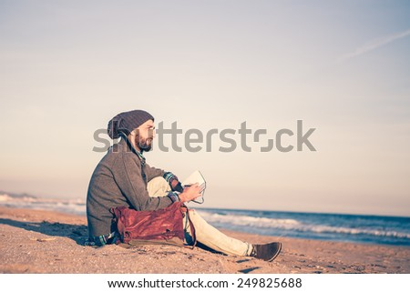 Man work on notebook at the beach at sunset - stock photo