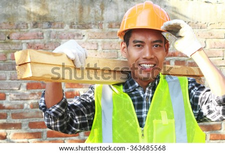 Man worker carrying wood smiling look on your camera with wall in the background