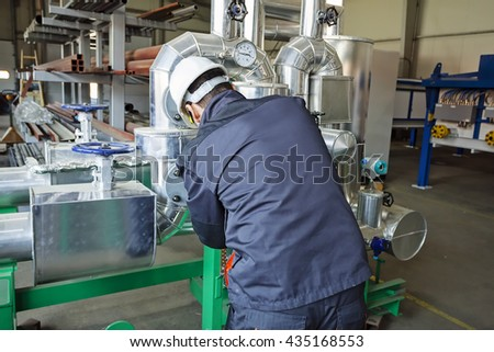 Man worker checking advanced industrial engine in the production hall