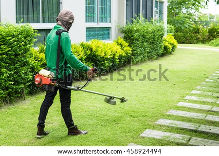 Man worker cutting grass with lawn mower.