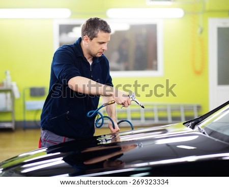 Man worker drying car on a car wash   - stock photo