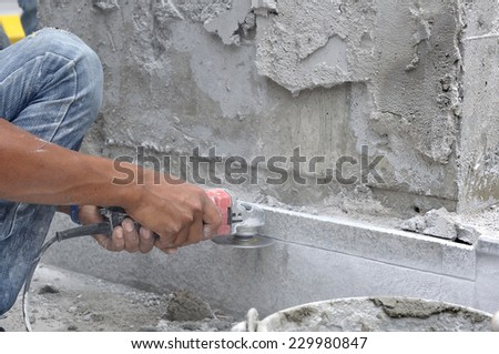 Man worker hands using electric grinder cutting stone.