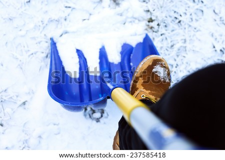 Man worker in uniform ,shoveling snow - stock photo