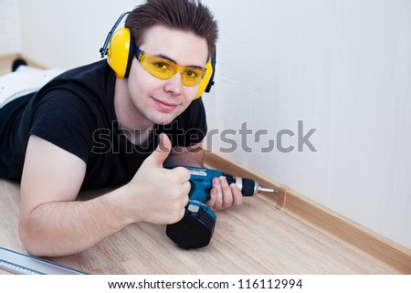 Man worker installing plinth on balcony. - stock photo