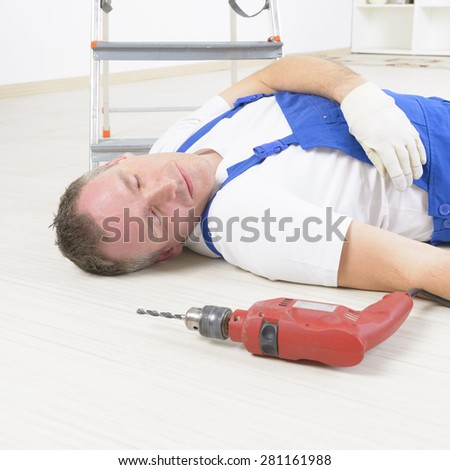 Man worker laying on a floor, concept of accident at work - stock photo