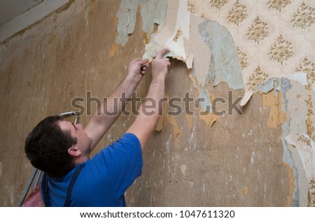 Man Worker Removing Old Wallpaper Of A Concrete Wall During Renovation House