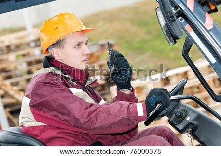 man worker sitting in industrial stacker forklift at warehouse using radio transmitter