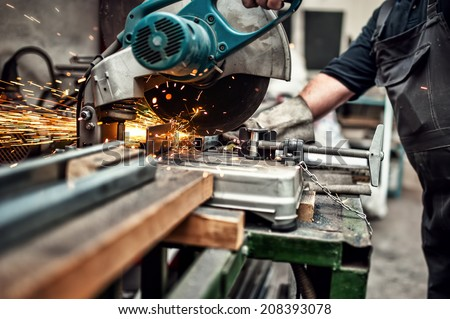 man, worker using a sliding compound mitre saw with circular blade for cutting metal and plastic - stock photo