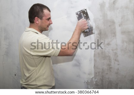Man worker using builders float to apply first layer of putty for wall