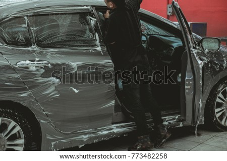 Man worker washing car by pressurized water and foam