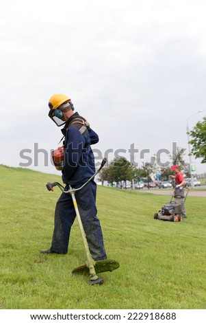 Man workers city landscapers starting gas trimmer and lawn mower equipment   - stock photo