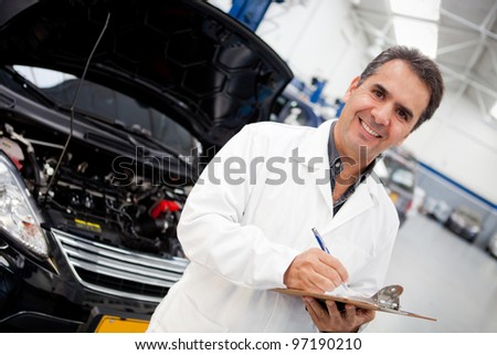 Man working as mechanic in a car garage and taking notes - stock photo