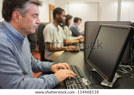 Man working at computer in computer class - stock photo