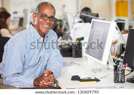 Man Working At Desk In Busy Creative Office - stock photo