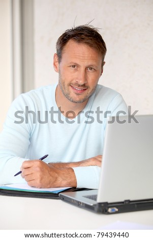 Man working at home on laptop computer - stock photo