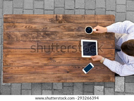 Man working at vintage rough wooden desk directly from above browsing electronic gadget drinking coffee mobile office phone paved road on background casual dress code white shirt - stock photo