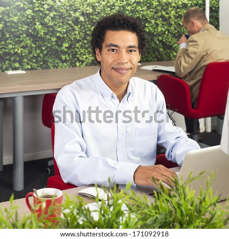 Man, working behind a laptop in a shared office space - stock photo