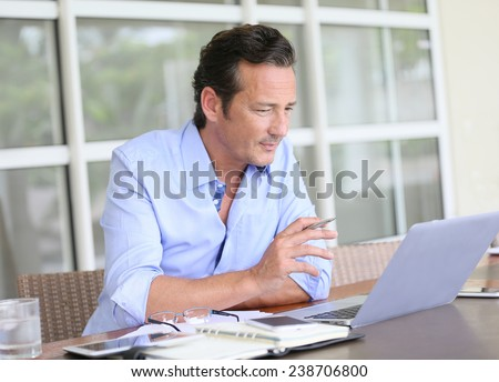 Man working from home on laptop computer - stock photo