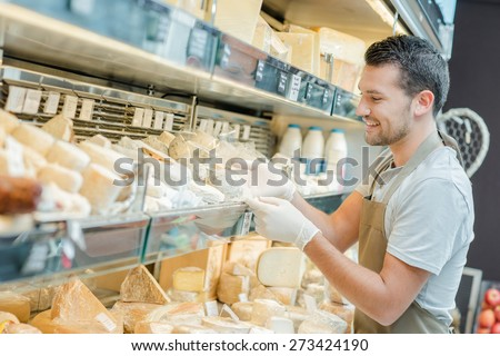 Man working in a cheese shop - stock photo