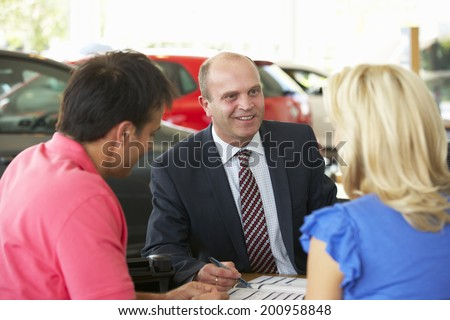 Man working in car showroom - stock photo