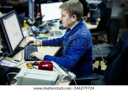 Man working in office in front of desktop computer - stock photo