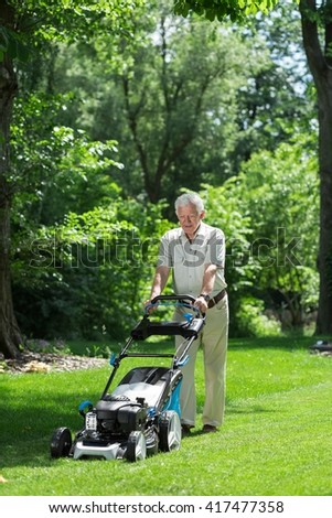 Man working in the garden using a lawnmower
