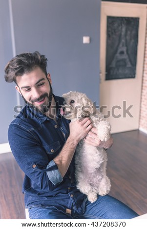 Man working in the office and holding his little dog. - stock photo