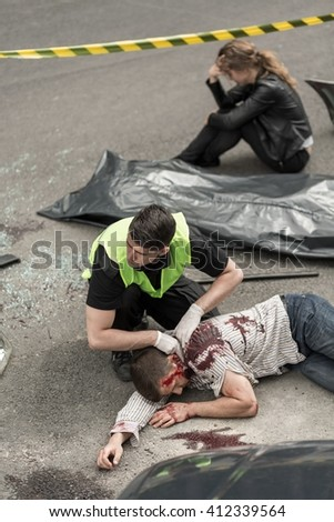 Man working in the scene of the accident, body lying on street, despair woman sitting in the background - stock photo