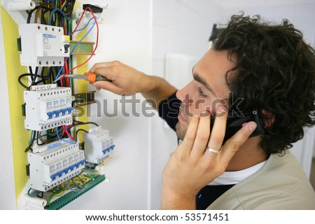 Man working on a circuit breaker and phoning - stock photo
