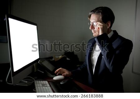 man working on a computer in dark room with screen illuminating his face. - stock photo