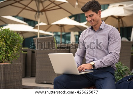 Man working on a computer outdoors.