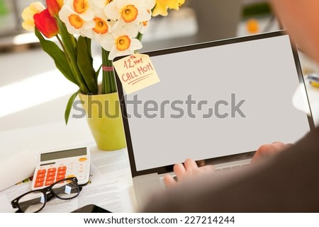 Man working on a laptop. Having reminder on his monitor to call mom for Mother's Day. - stock photo