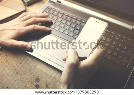 Man working on a laptop on a wooden table