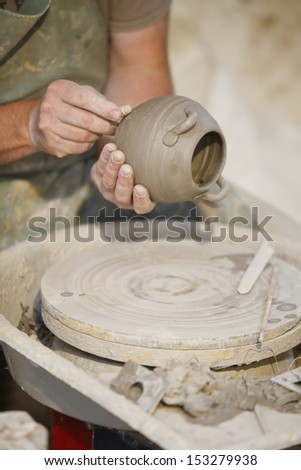 Man working on a pot with pottery wheel - stock photo