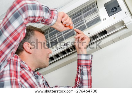 Man working on air conditioning unit - stock photo