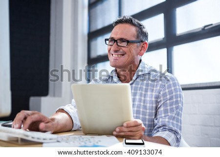 Man working on computer and holding digital tablet in office - stock photo