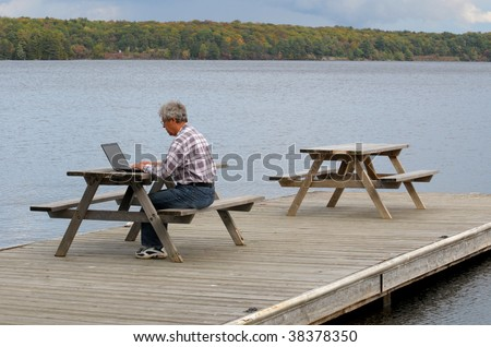 Man working on computer at a dock - stock photo