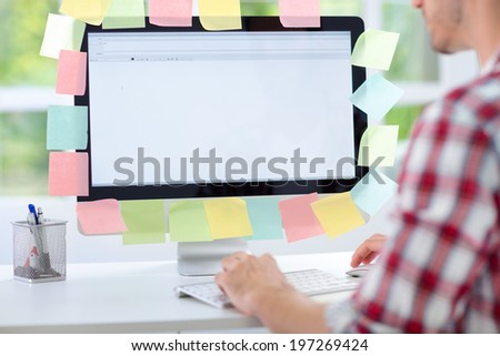 Man working on computer with sticky notes, back view  - stock photo
