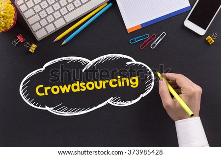 Man working on desk and writing Crowdsourcing - stock photo